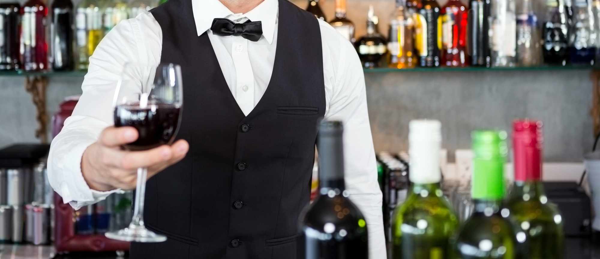 bar server handing over a glass of red wine
