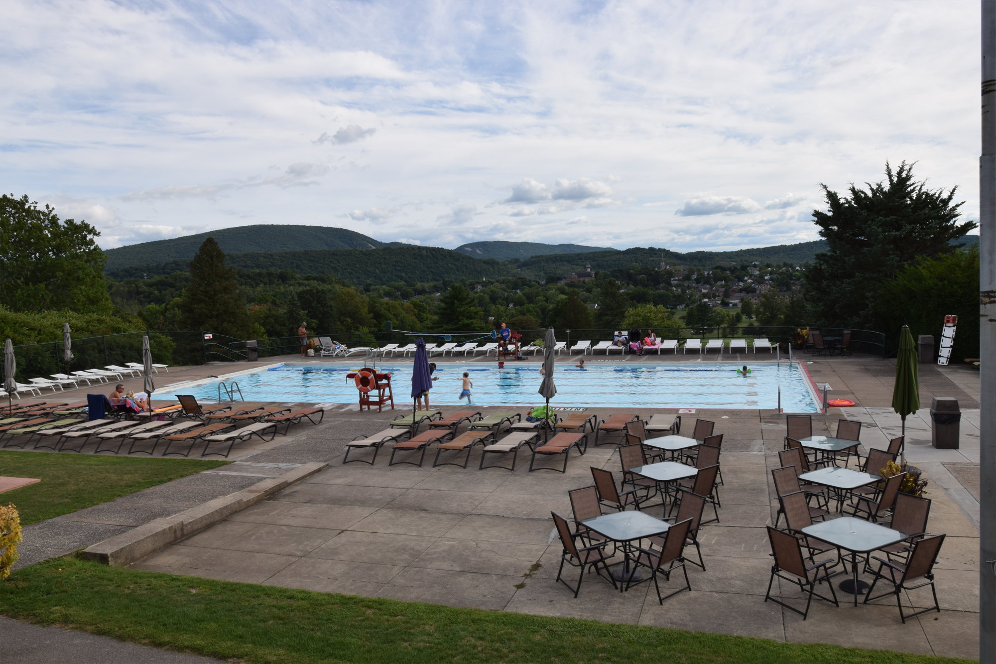 Blairmont Club pool with many lounge chairs and patio tables with scenic view of Hollidaysburg